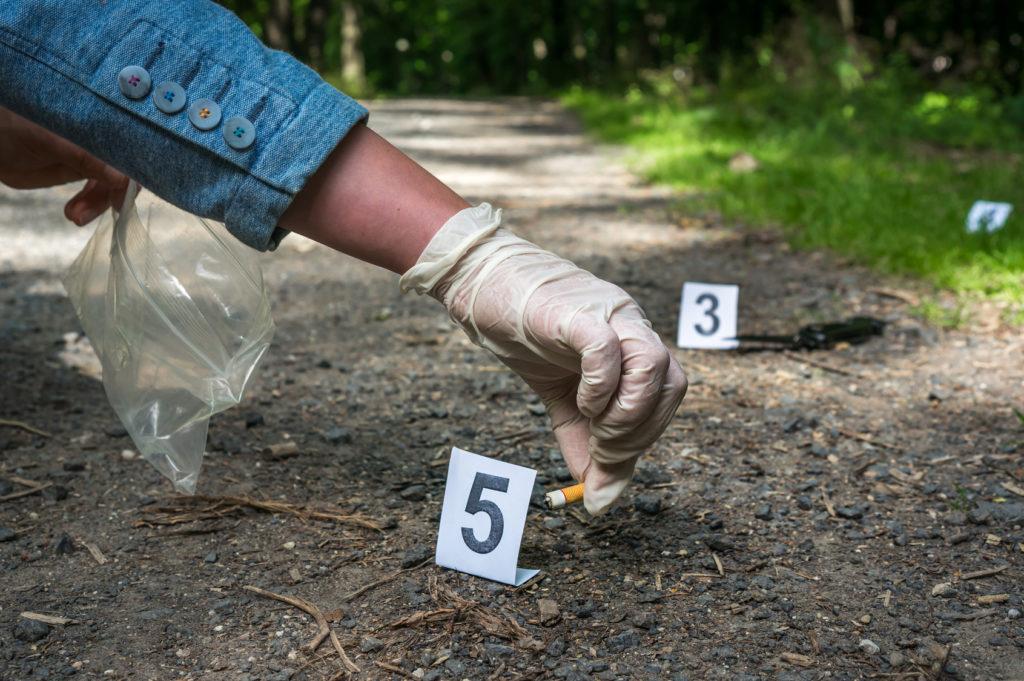 Odkrywanie i zabezpieczanie śladów - niedopałek papierosa - na miejscu zdarzenia