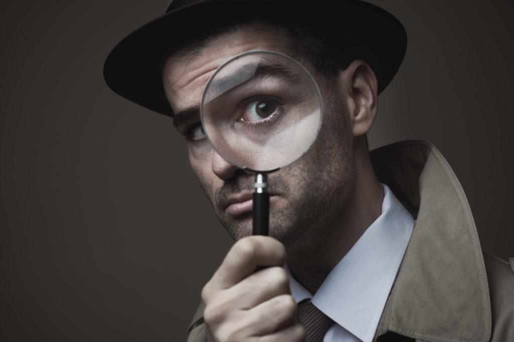 Detektyw trzymający komicznie dużą lupę przy oku